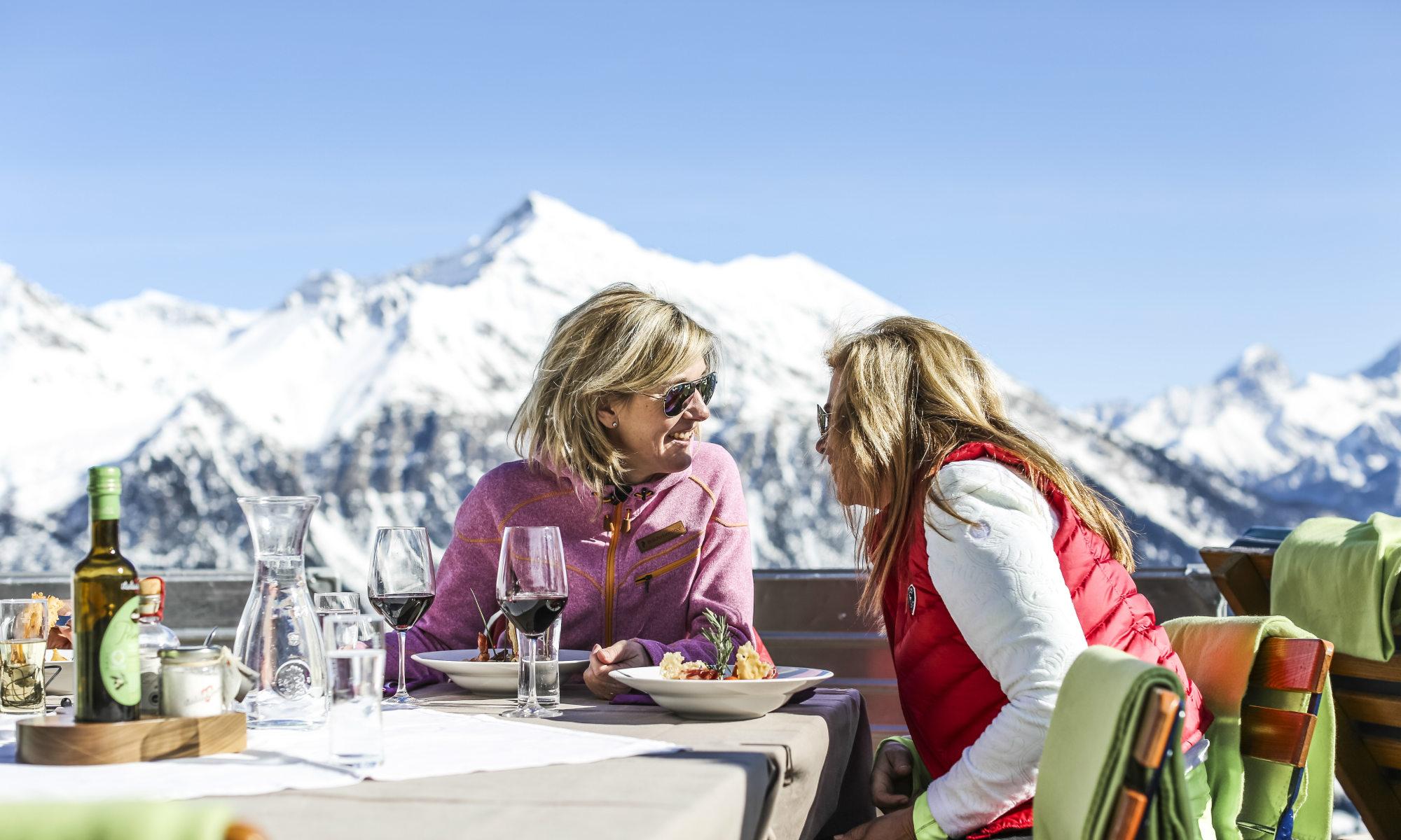 2 Frauen genießen nach einem Skikurs für Erwachsene eine Mahlzeit in einem Bergrestaurant in Lenzerheide.