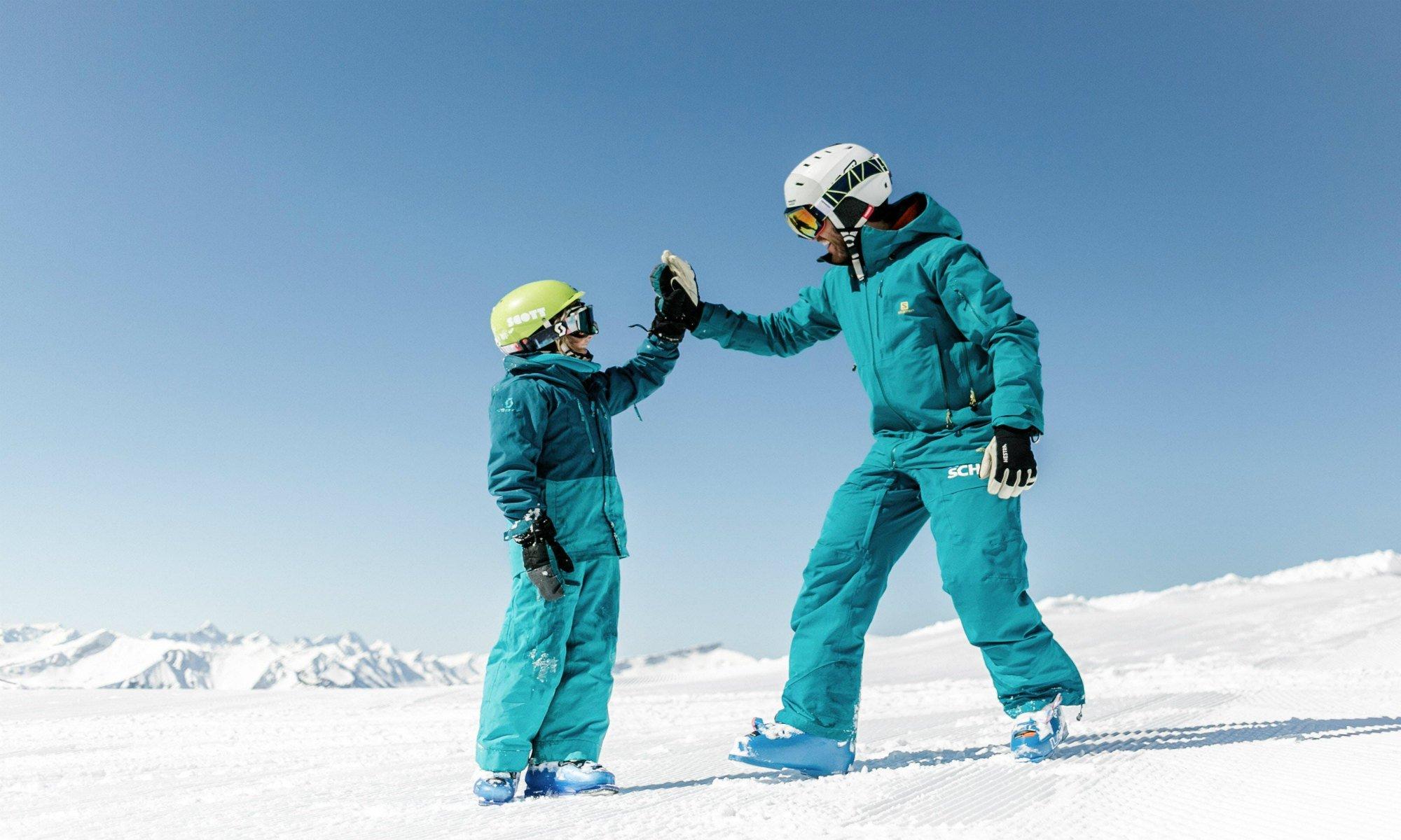 Een skileraar geeft zijn leerling een high five tijdens een skiles in het skigebied van Oberstdorf.