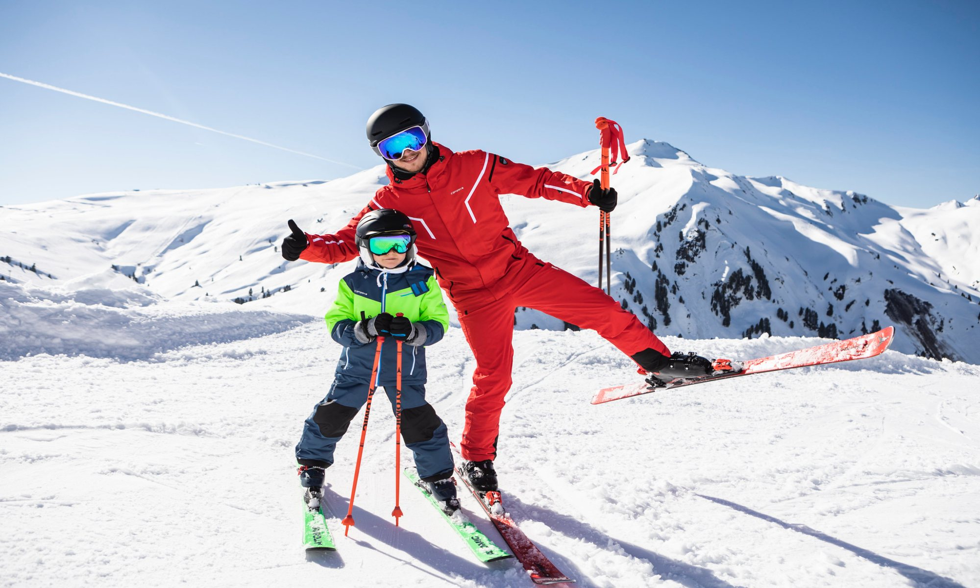 A young skier and his ski instructor on the snowy slopes.