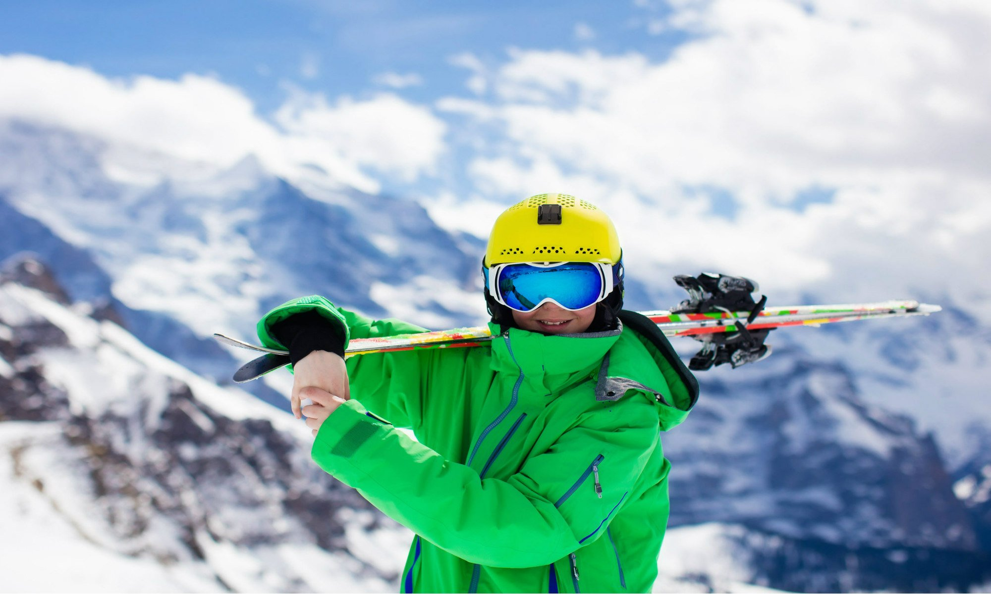 Smiling teenage skier with a snowy mountain backdrop.