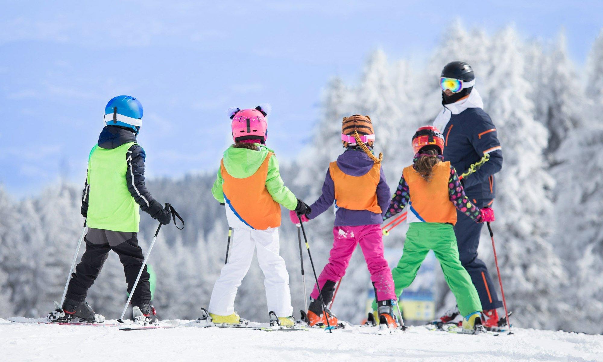 Een groep jonge skiërs luisteren aandachtig terwijl ze leren skiën in Winterberg.