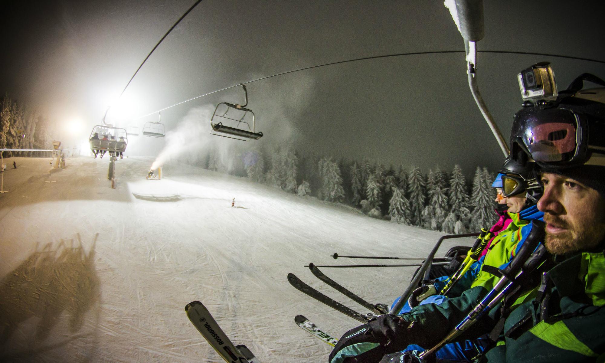 Skiërs hebben vanuit een skilift uitzicht op een verlichte piste in Winterberg.