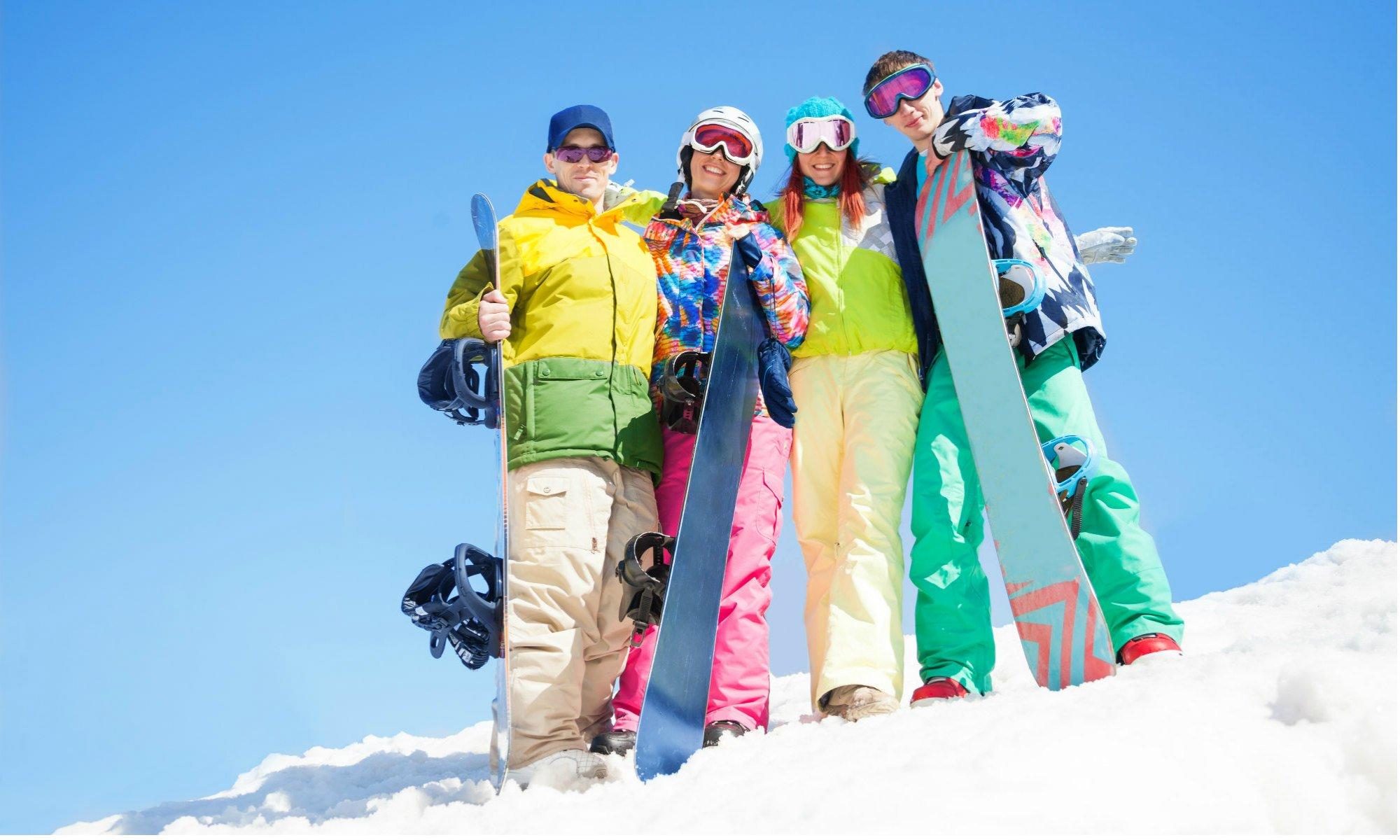 Un gruppo di amici in posa sulla neve con i loro snowboard.