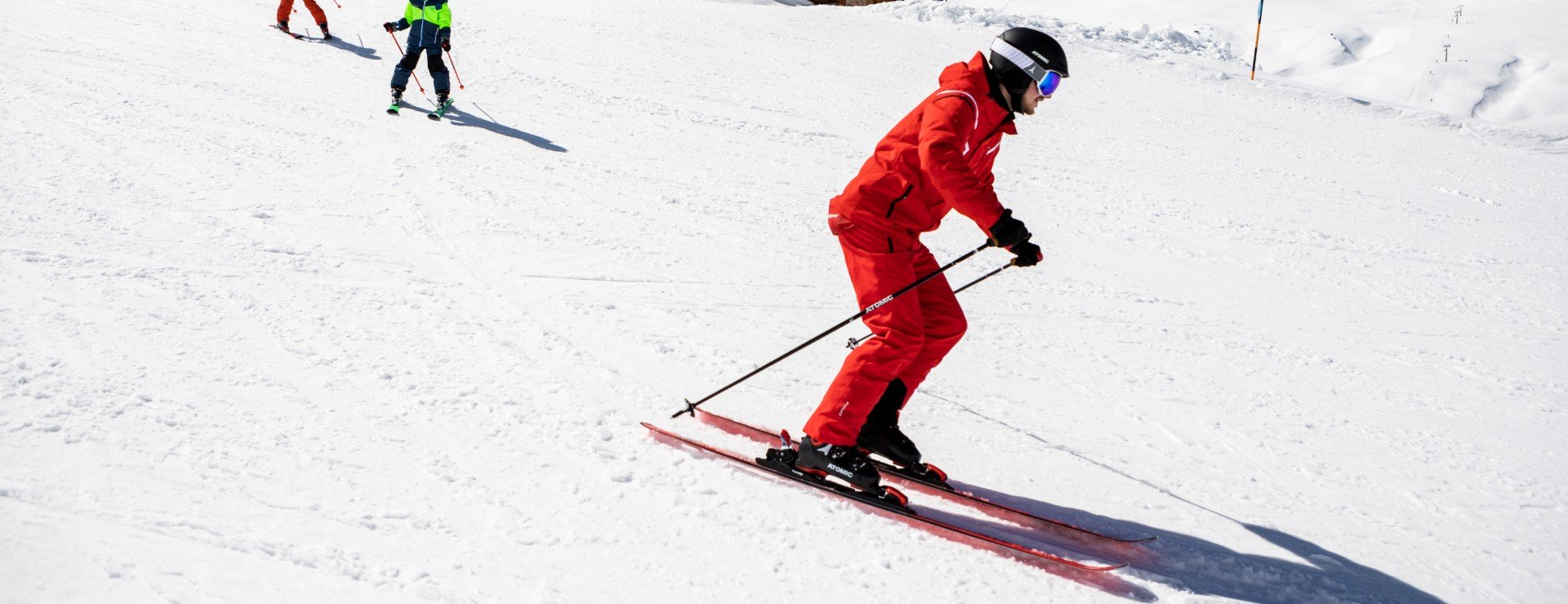 A ski instructor is showing the parallel turns technique.