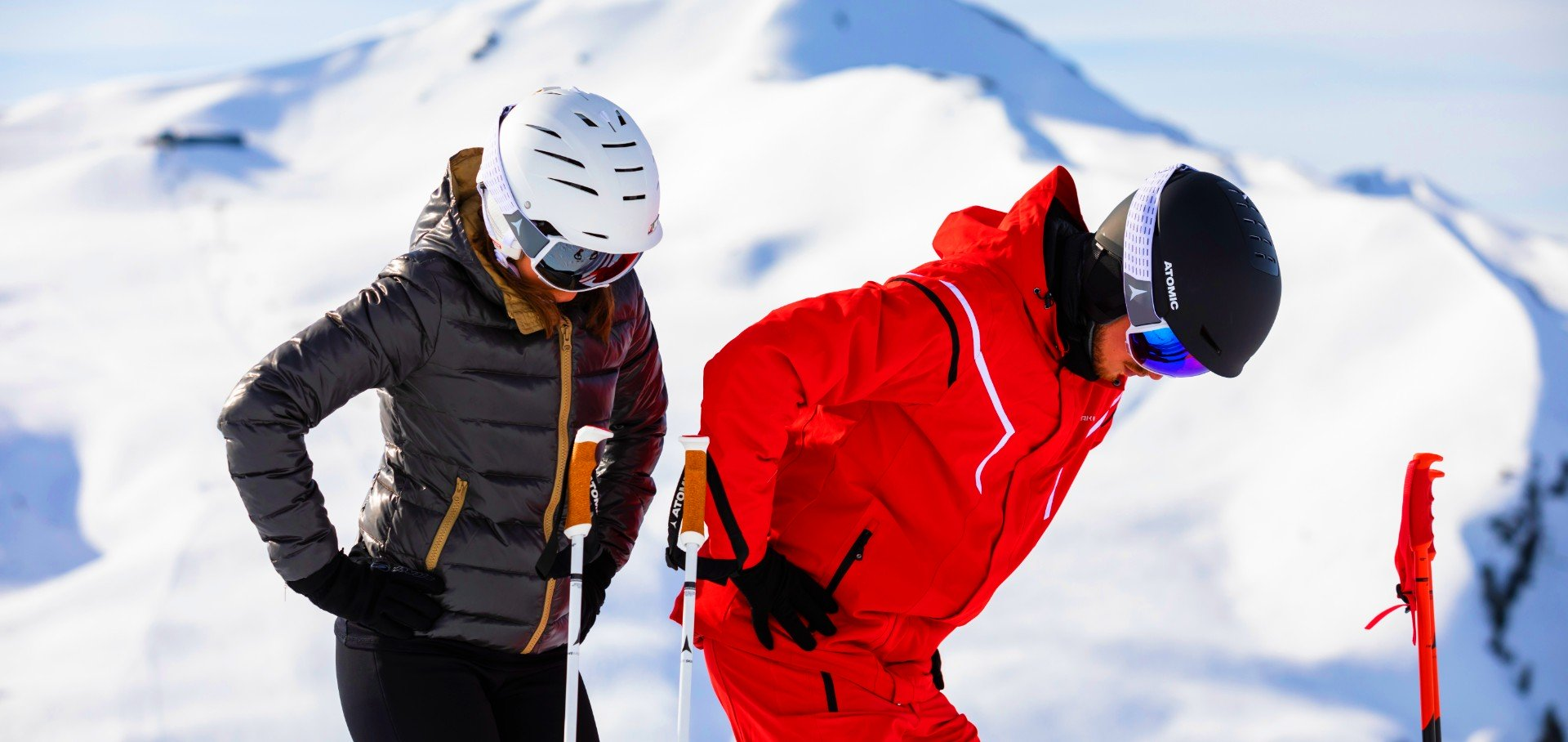 A ski instructor is showing a girl the posture to keep while skiing.