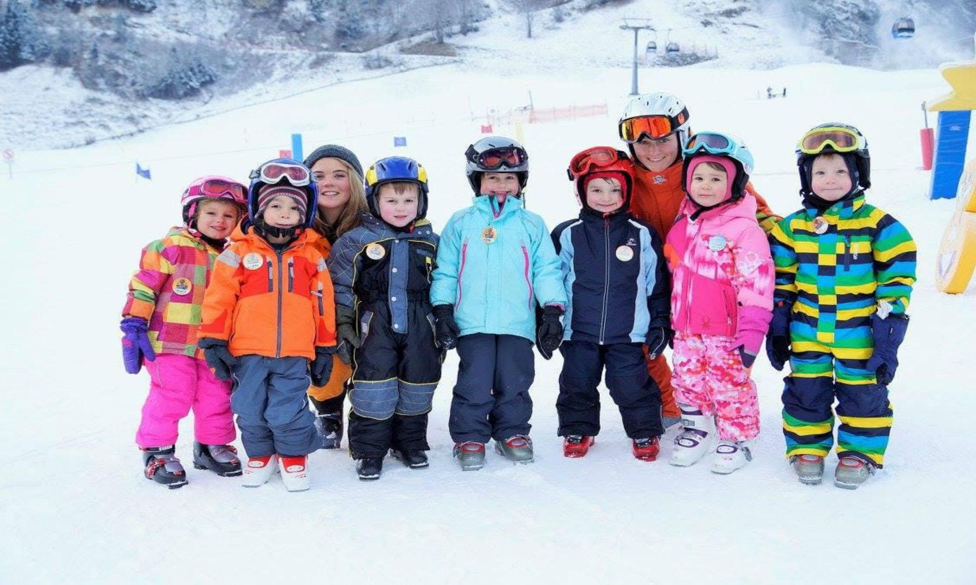 Twee skileraressen poseren voor een foto met hun jonge leerlingen in het skigebied van Rauris.