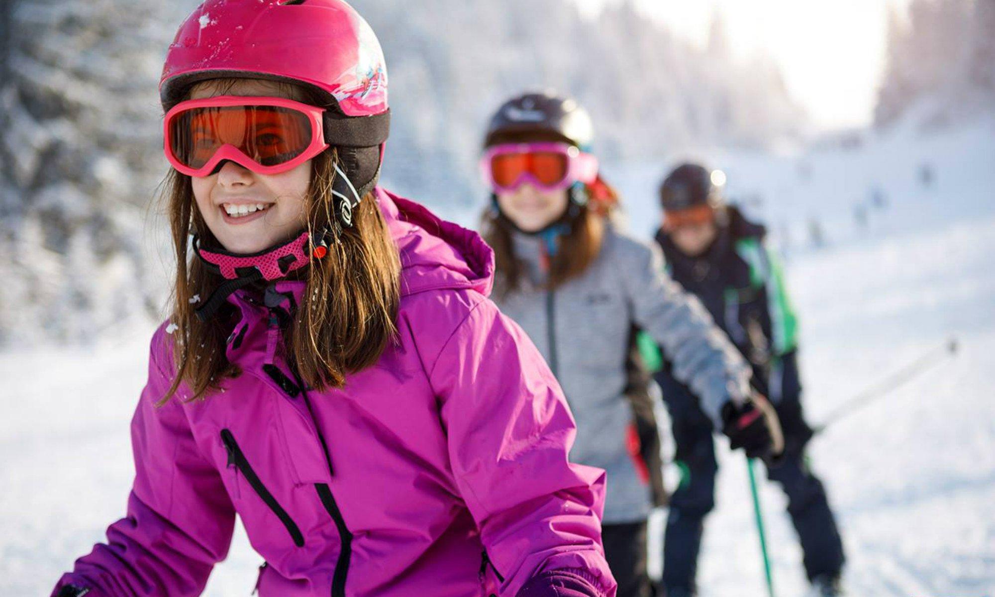 Drie kinderen nemen deel aan een skiles in het skigebied van Willingen.