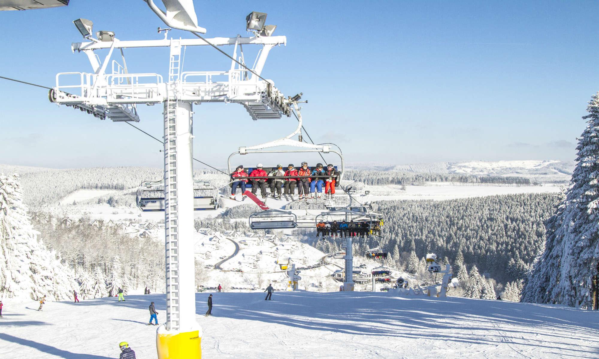 Blik op een stoeltjeslift en een winters landschap in het skigebied van Winterberg.