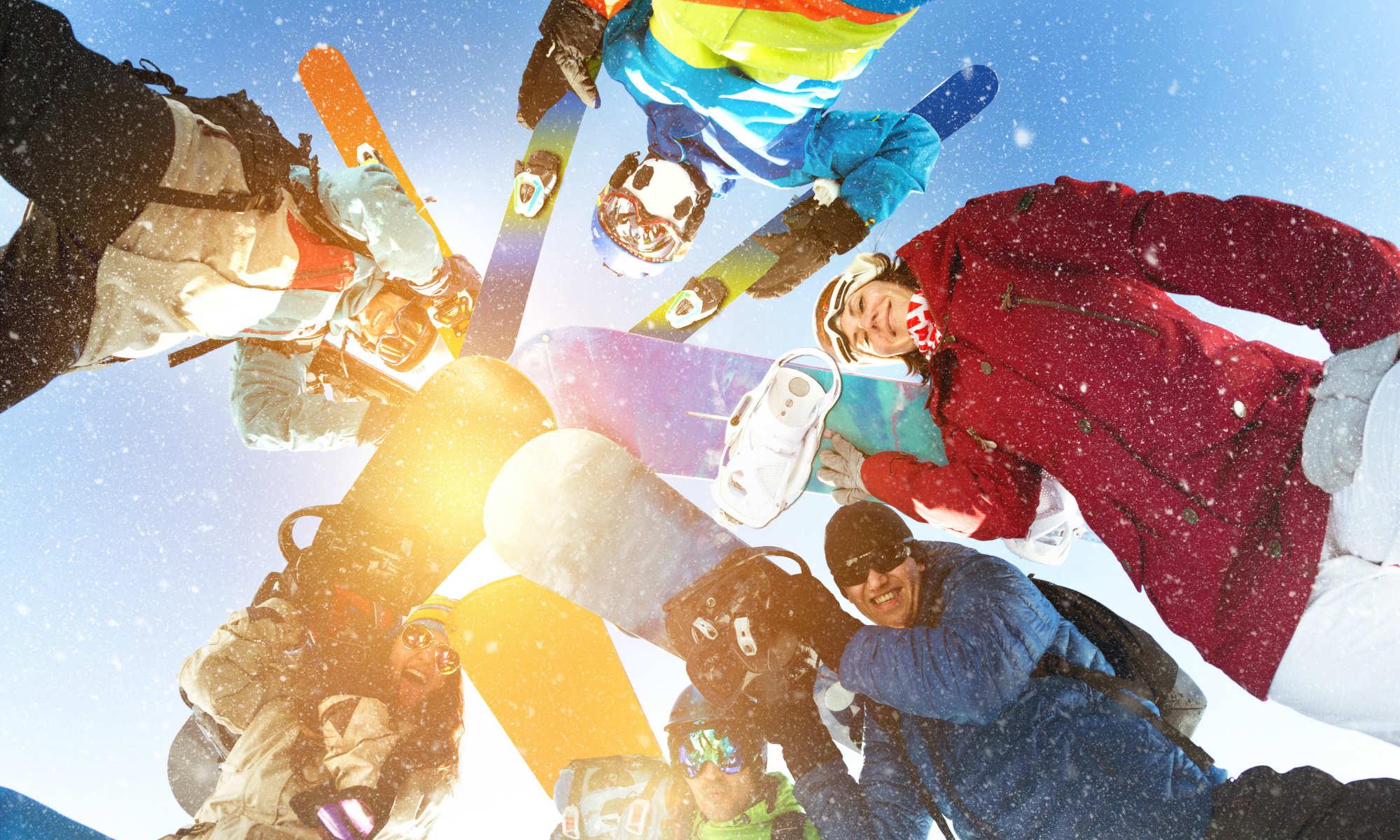 Un gruppo di amici sulla neve, posizionati in cerchio attorno alla macchina fotografica, posano con i loro sci e snowboard, sorridendo.