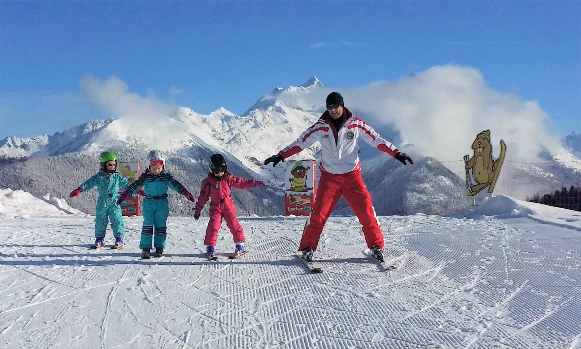 Un maestro di sci mostra a 3 piccoli allievi come restare in piedi sugli sci.