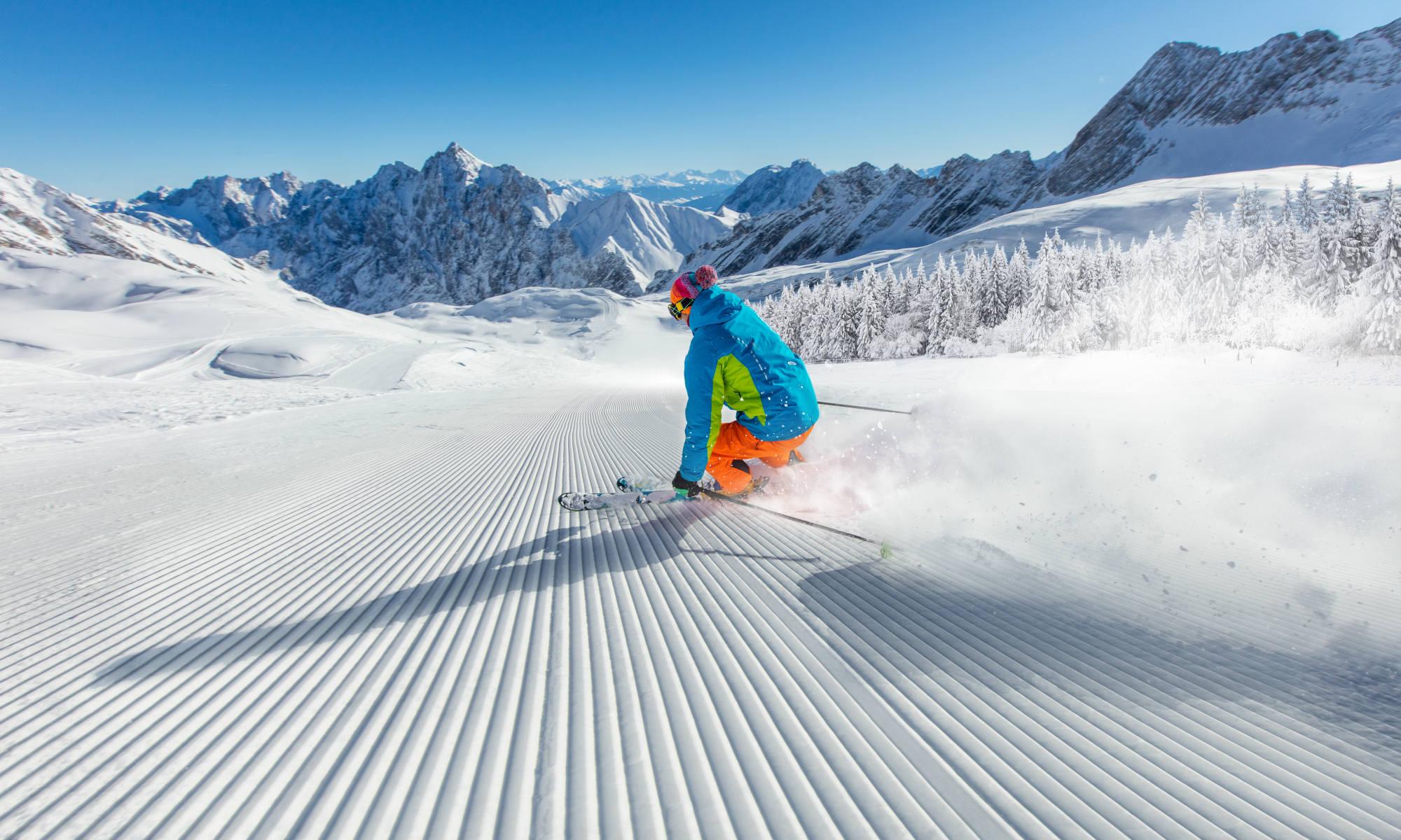 Uno sciatore scivola lungo una pista vuota, con le Dolomiti sullo sfondo.