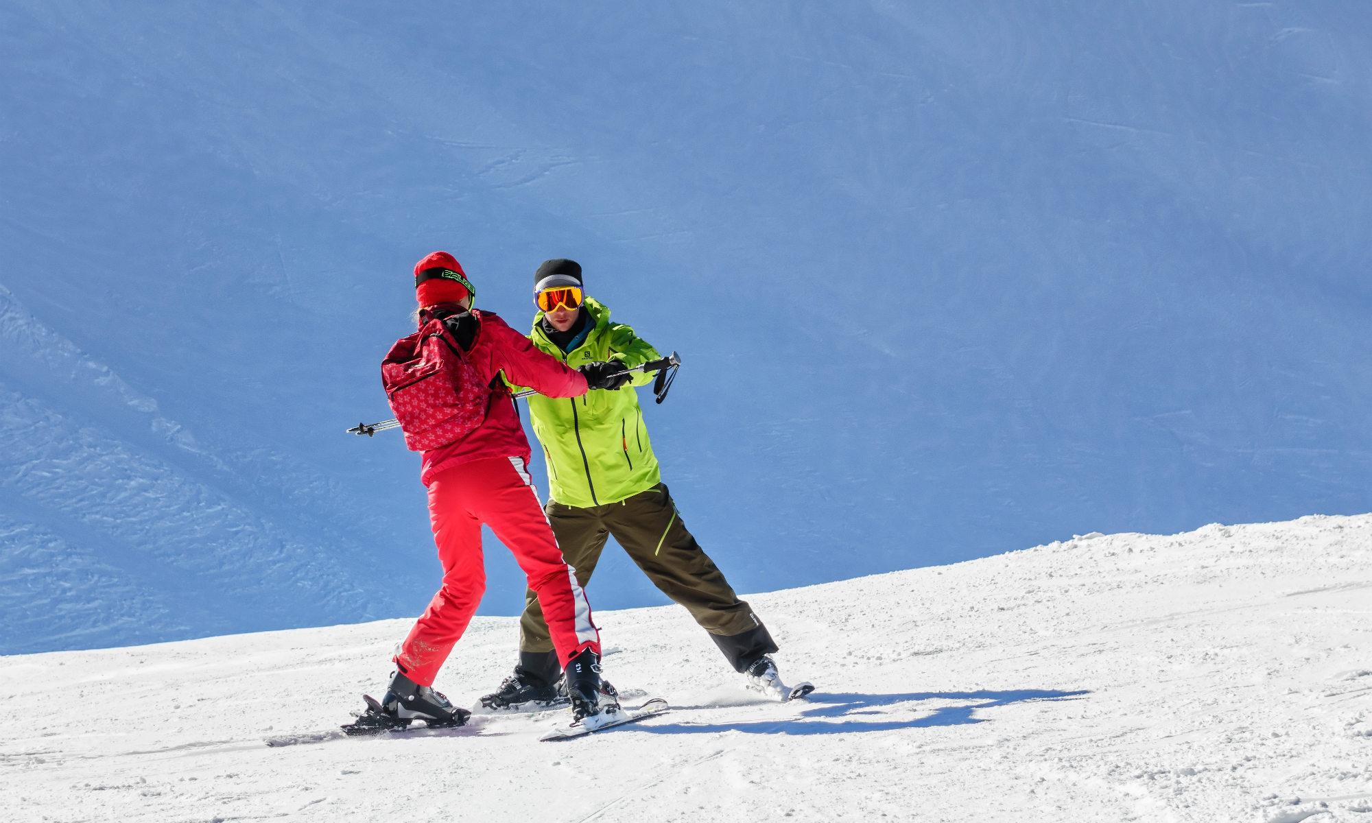 Un istruttore privato aiuta un allievo a mantenere la posizione sugli sci con l'aiuto di una racchetta da sci.