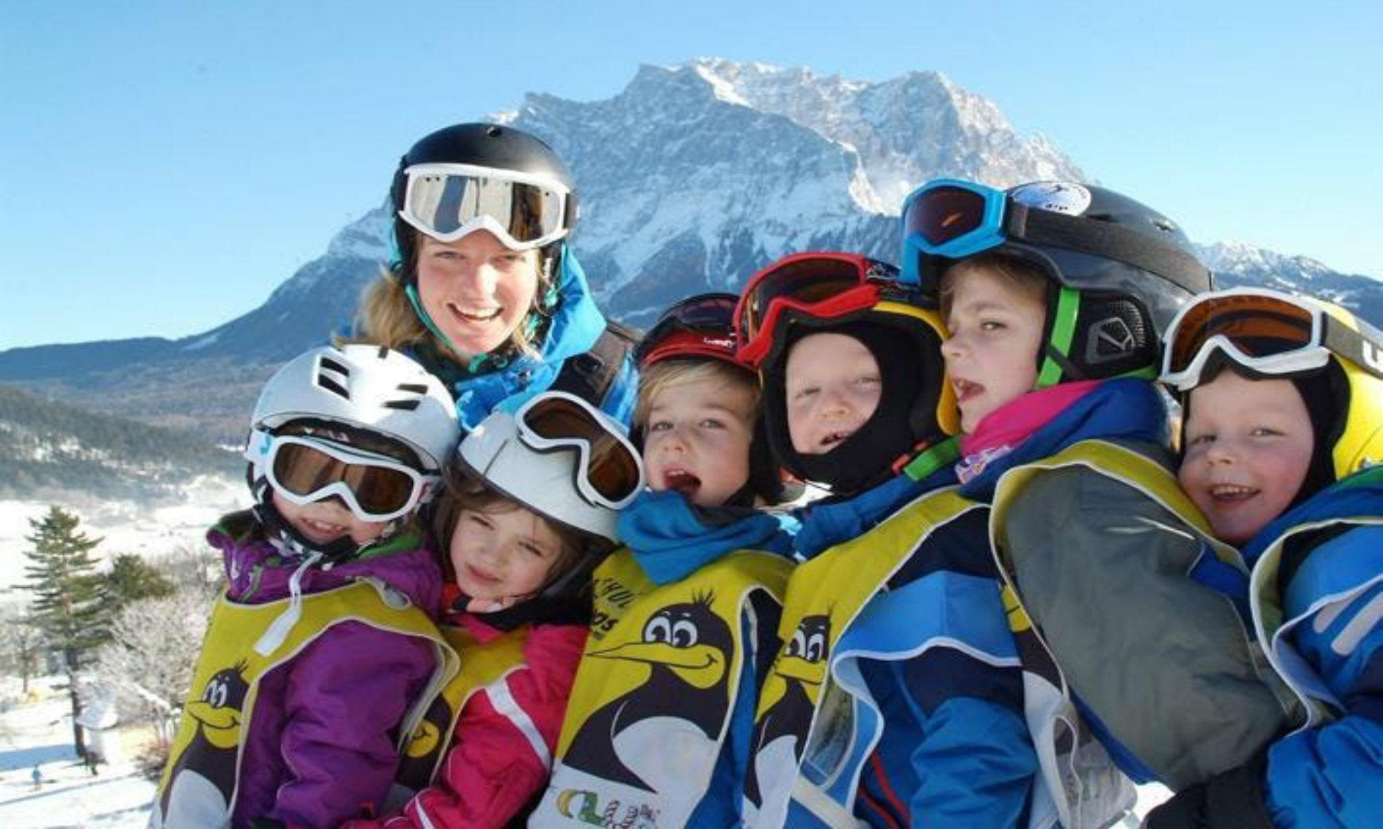 Een groep leerlingen poseert voor een foto met hun skilerares in het skigebied van Ehrwalder Alm.
