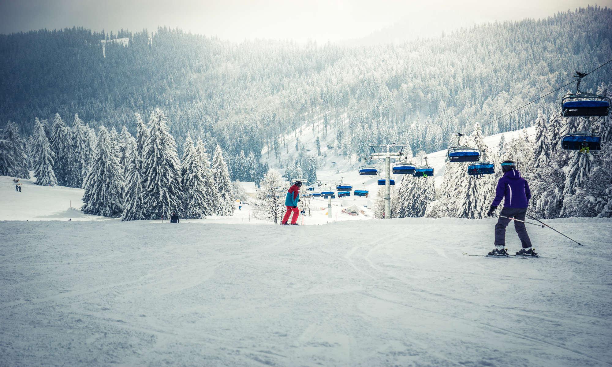 Twee skiërs zijn bezig aan een afdaling in het skigebied van Feldberg.