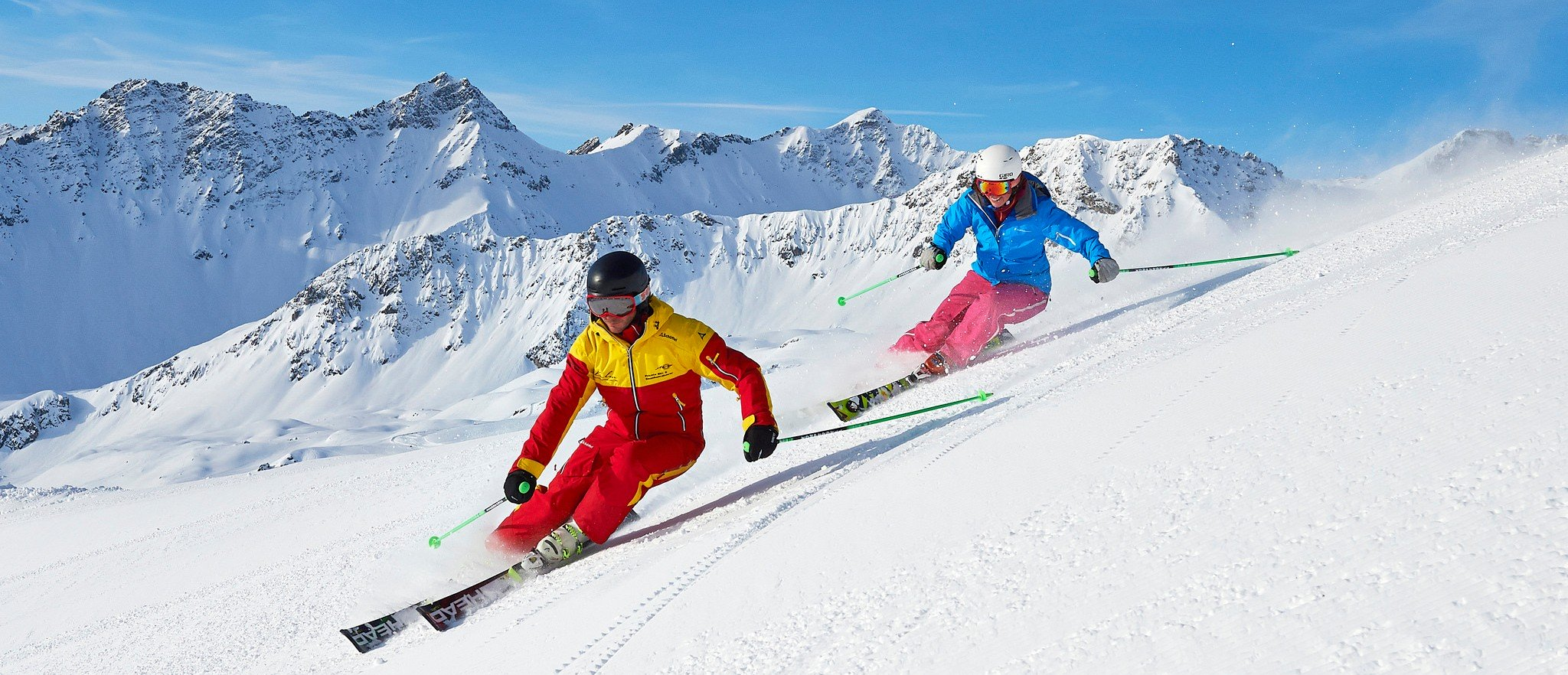 Two skiers show perfect skiing technique on the snowy slopes.