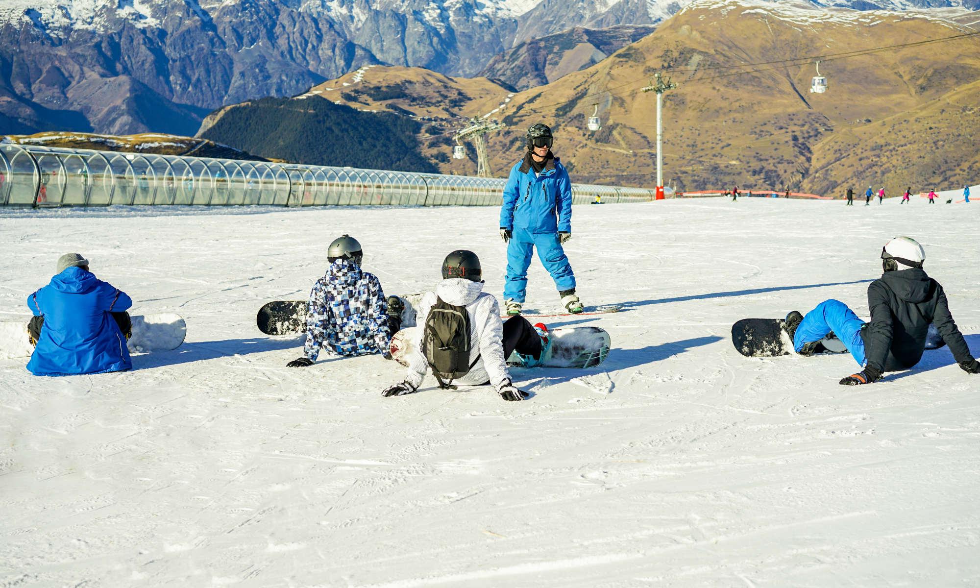 Un istruttore di snowboard spiega le basi a un gruppo di principianti seduti sulla neve con lo snowboard agganciato ai piedi.