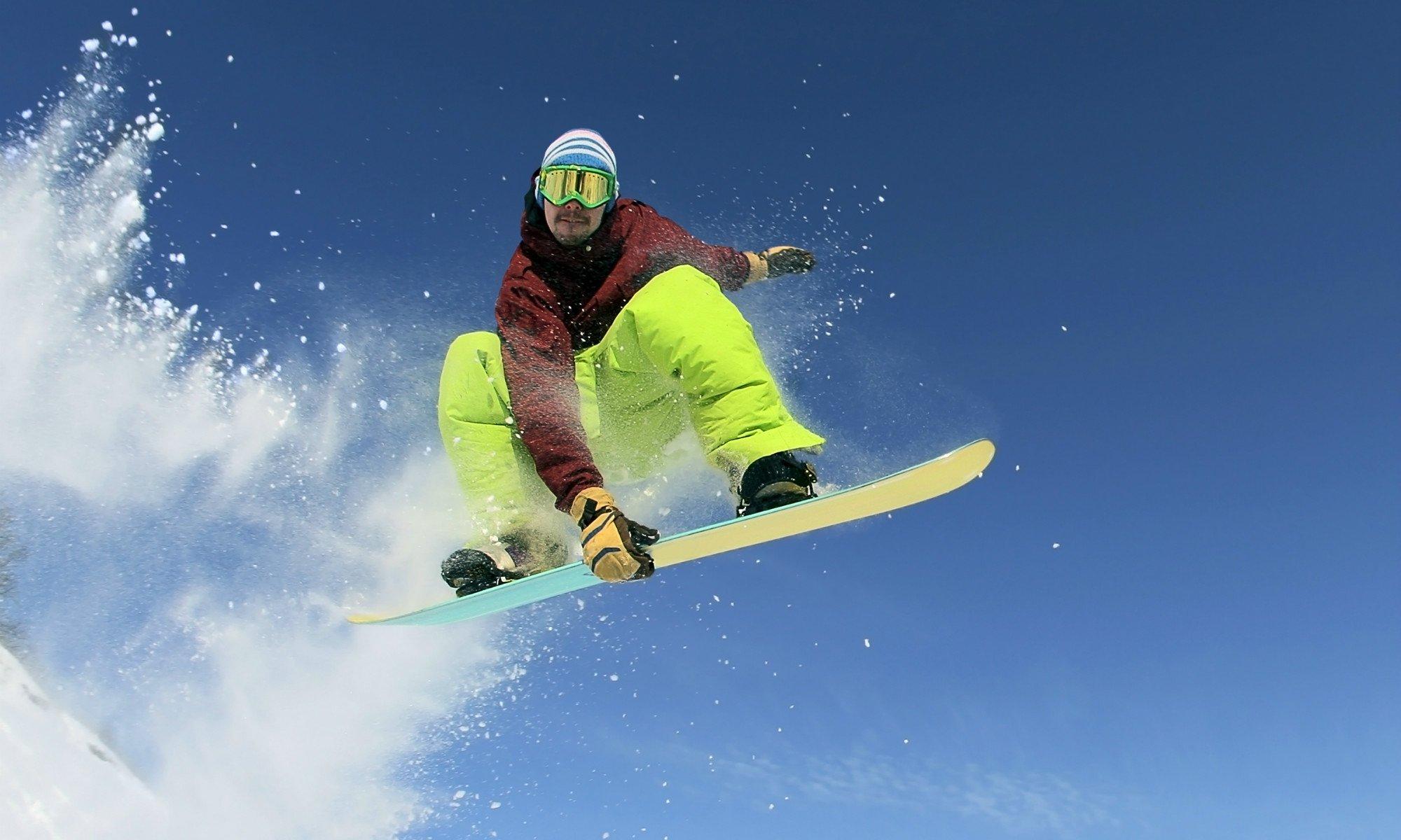 Un rider esperto posa verso la macchina fotografica mentre effettua un salto con il suo snowboard.