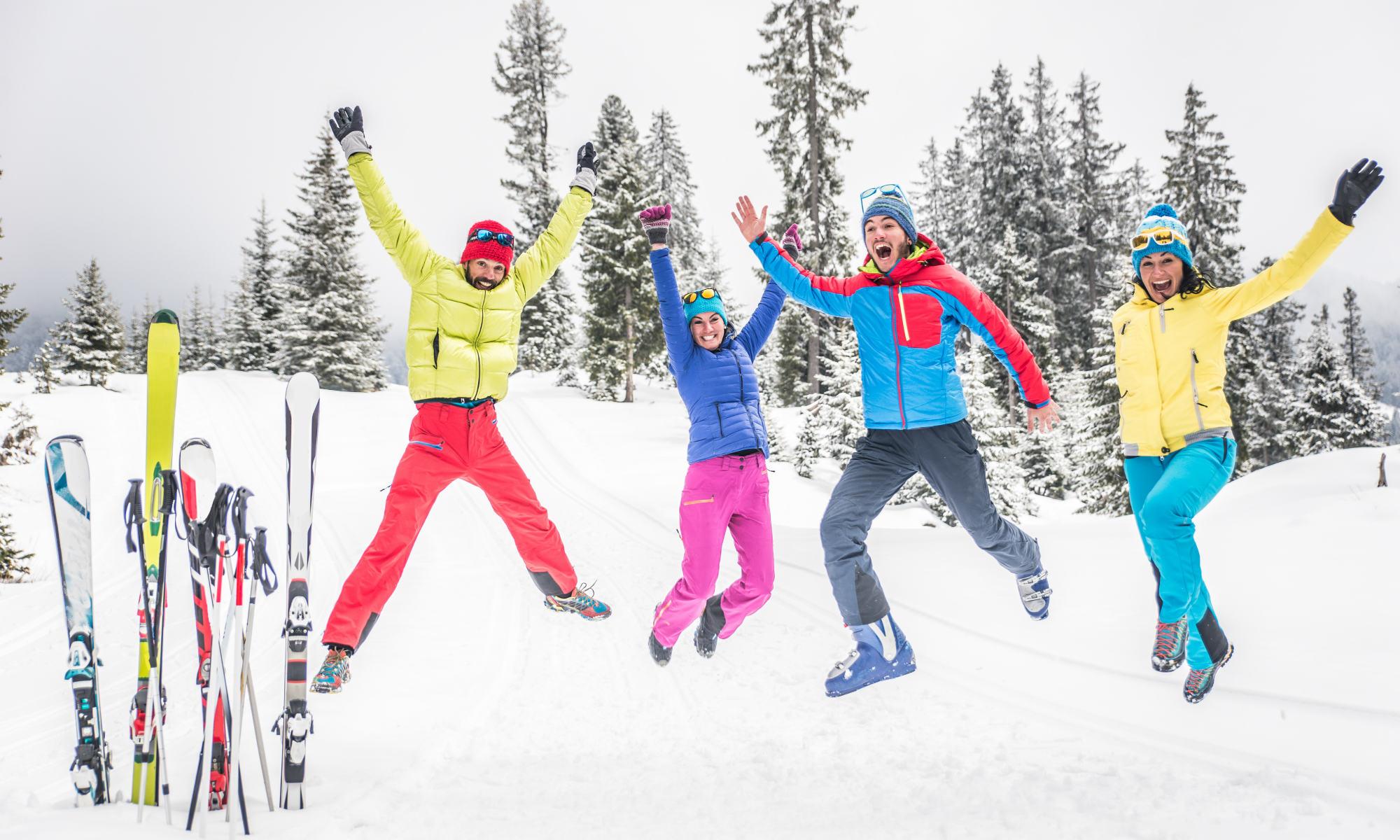 4 amici saltano sulla neve mentre posano per una foto, accanto alla loro attrezzatura da sci.
