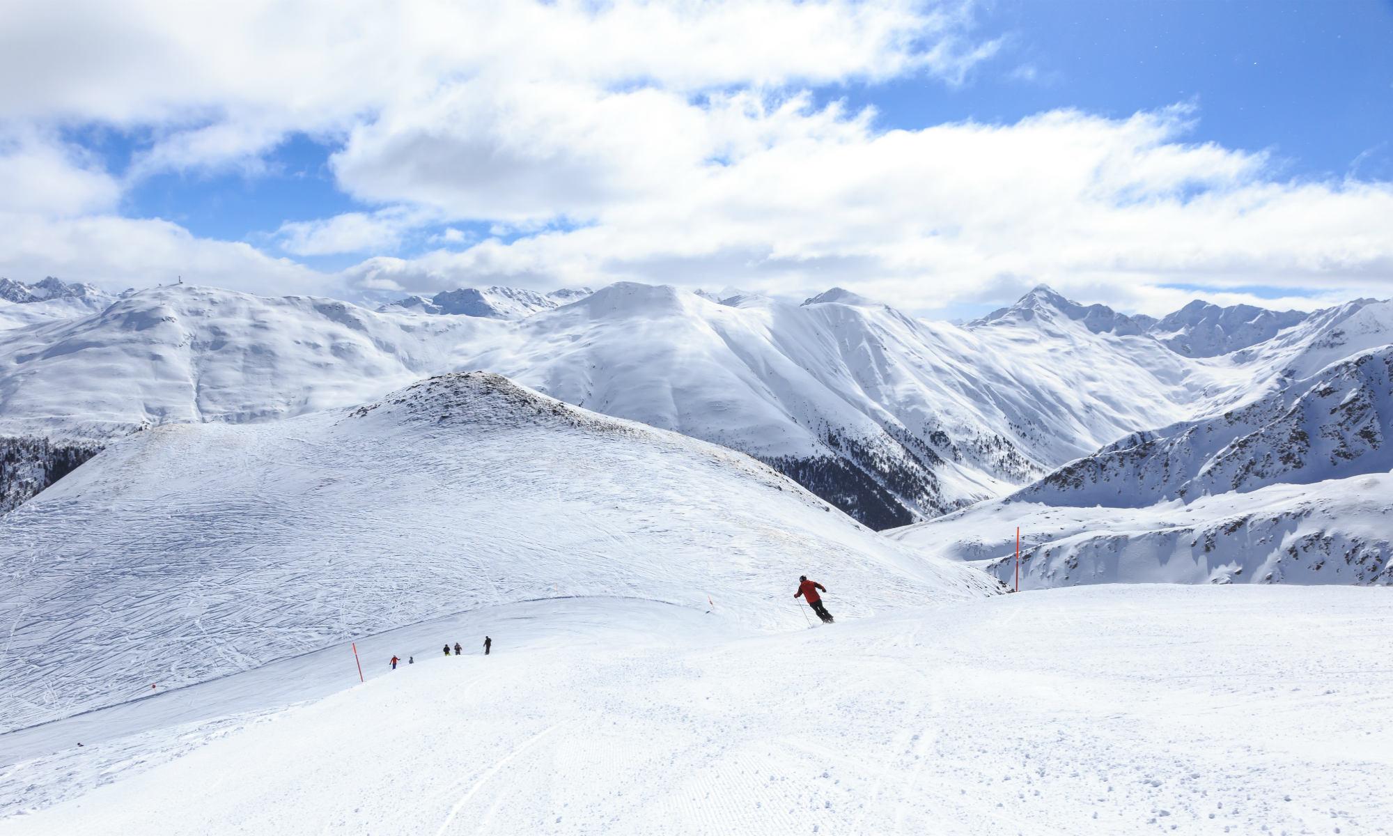 Uno sciatore lungo le piste vuote di una Livigno super innevata.
