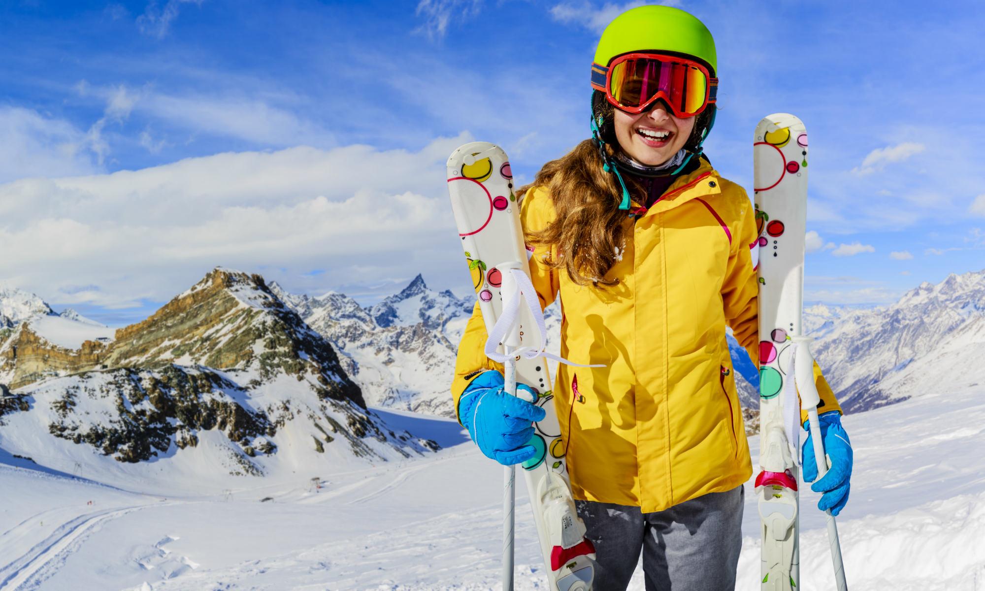 Una sciatrice con in mano la sua attrezzatura da sci, sorride verso la macchina fotografica.