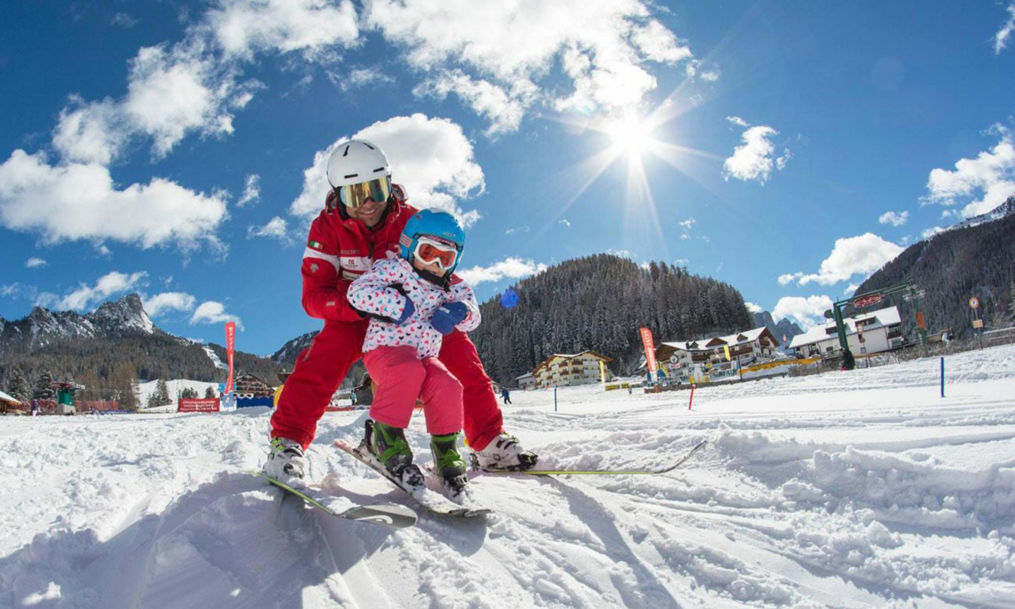 Un maestro di sci aiuta una piccola sciatrice a mantenere la posizione sugli sci.