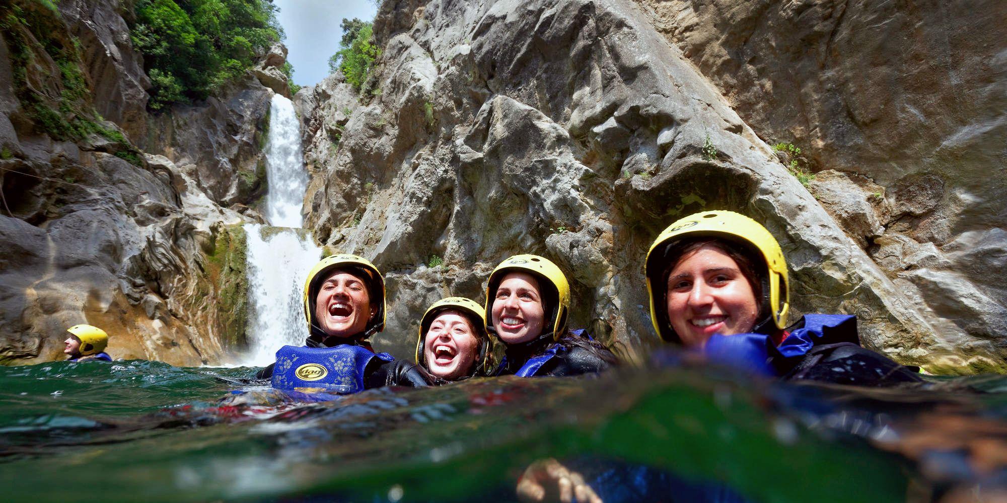 4 amis tout sourire dans l'eau au pied d'une cascade lors d'une activité de canyoning en Ardèche.