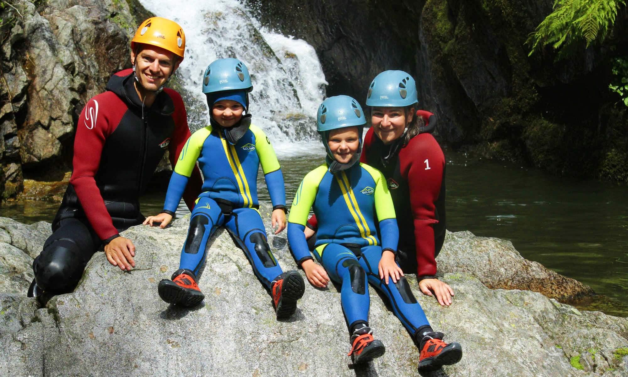 Une famille prend la pause dans le canyon de la Basse Besorgues devant une cascade.