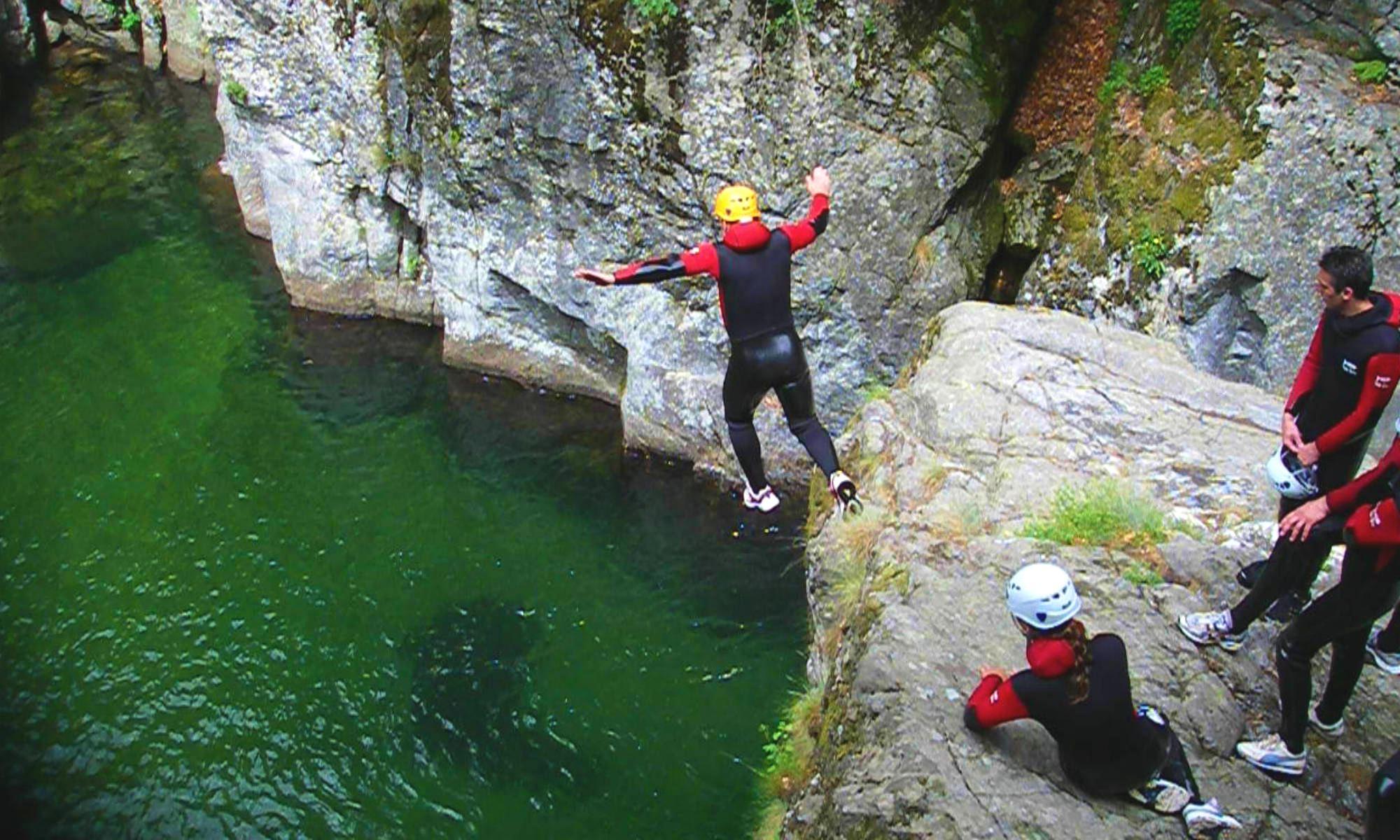 Un canyoniste saute dans l'eau du canyon de la Borne sous le regard de son groupe.