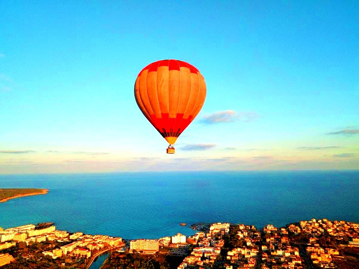 A hot air balloon flies over a town on the island of Mallorca.