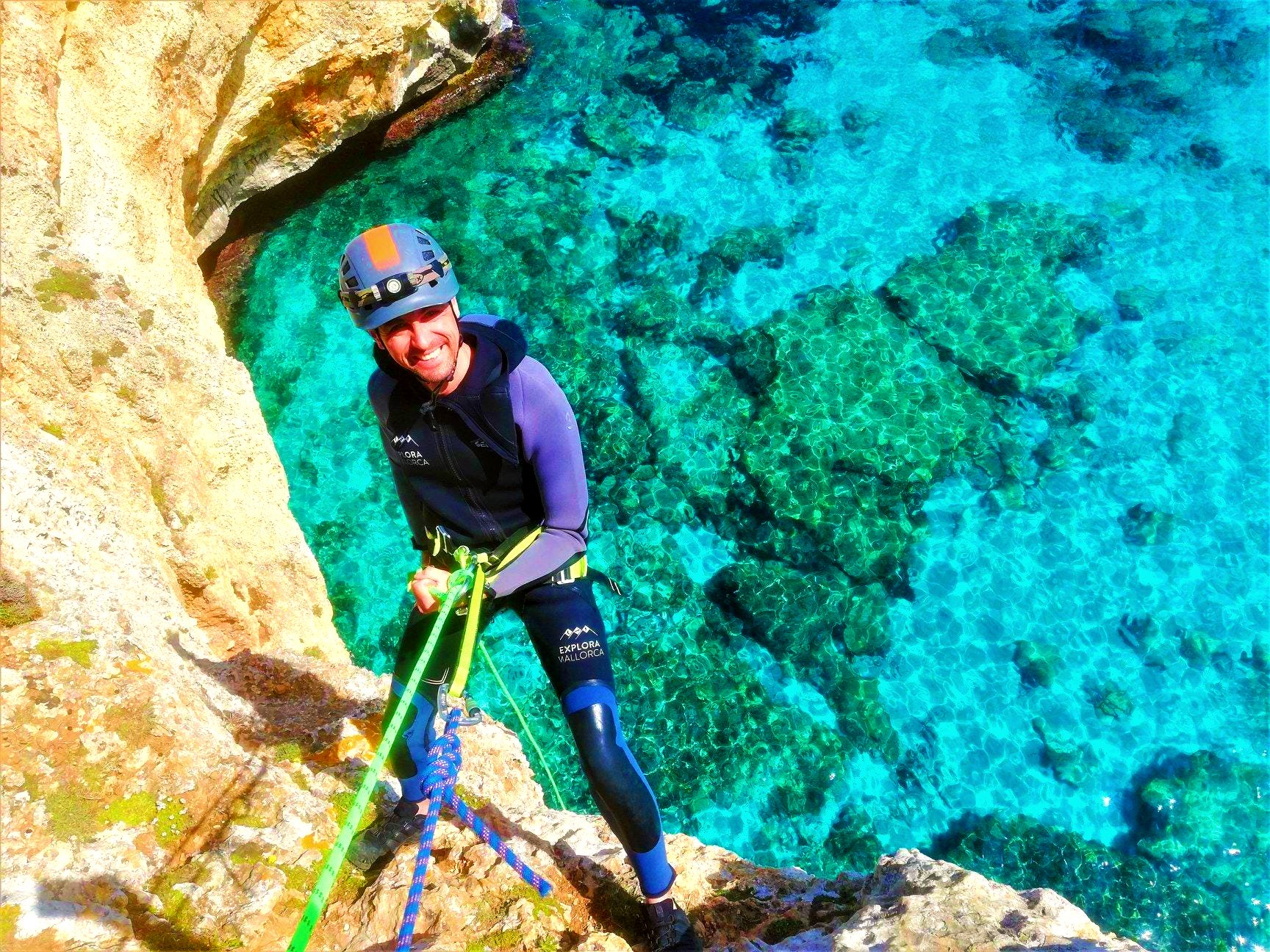 A guy is abseiling a cliff during Coasteering in Mallorca.
