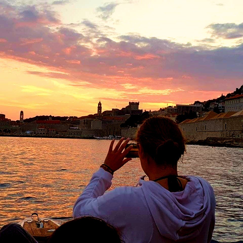 A tourist takes a picture of the city of Dubrovnik during a boat trip.