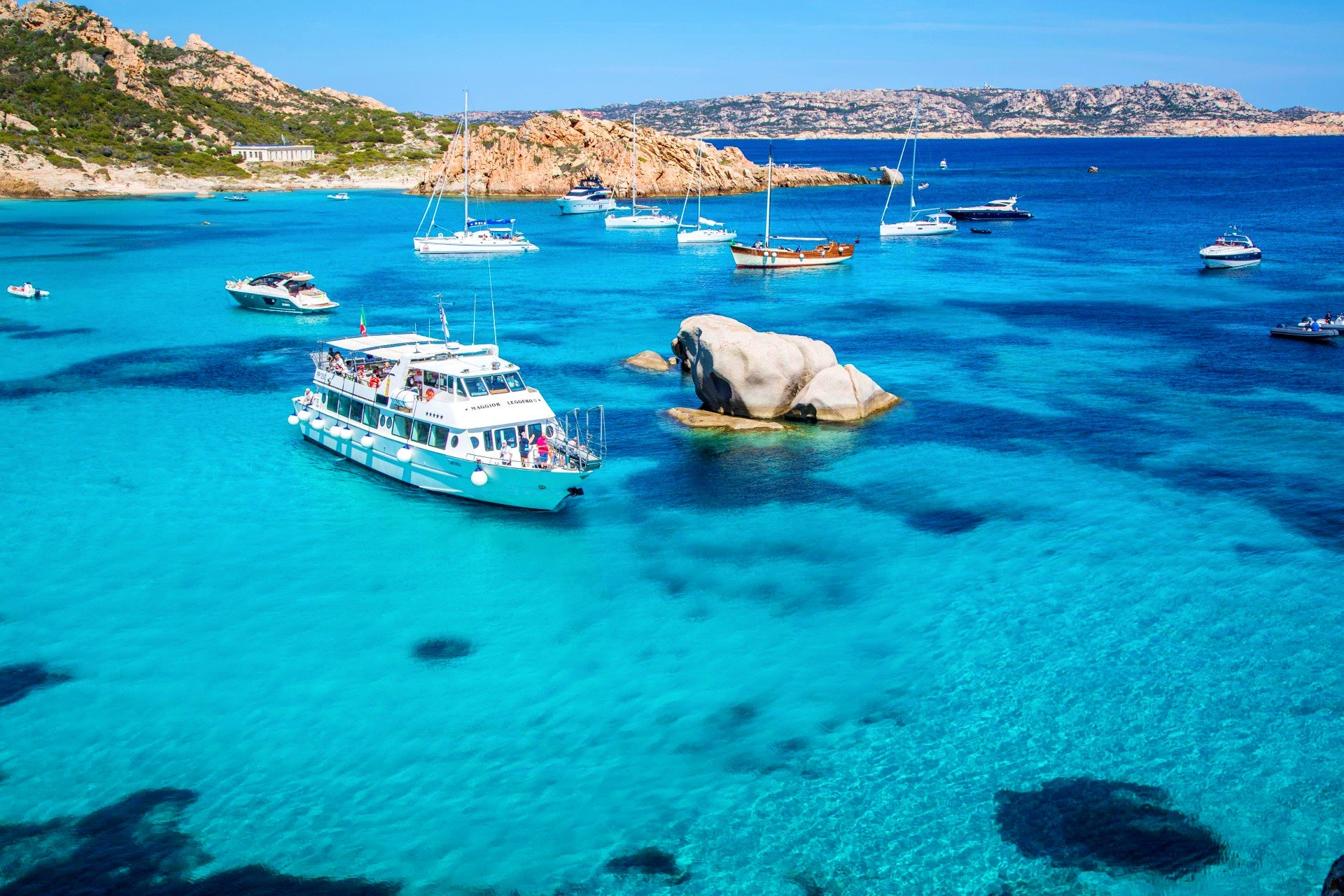 La barca Maggior Leggero mostra ai turisti la meravigliosa costa dell'arcipelago di La Maddalena durante un giro in barca di gruppo.