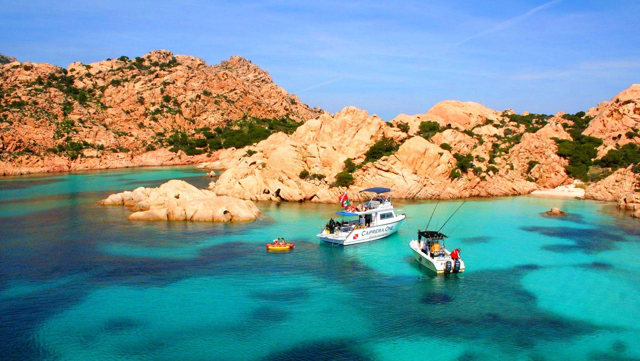 La barca di Orso Diving Club Poltu Quatu sta per gettare l'ancora vicino ad una spiaggia, durante il giro in barca dell'isola di Caprera.