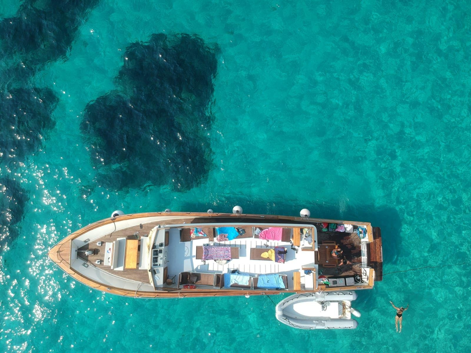 The boat Rocca Corsa is shown from above during a semi-private boat tour in La Maddalena, the sea around it is turquoise.