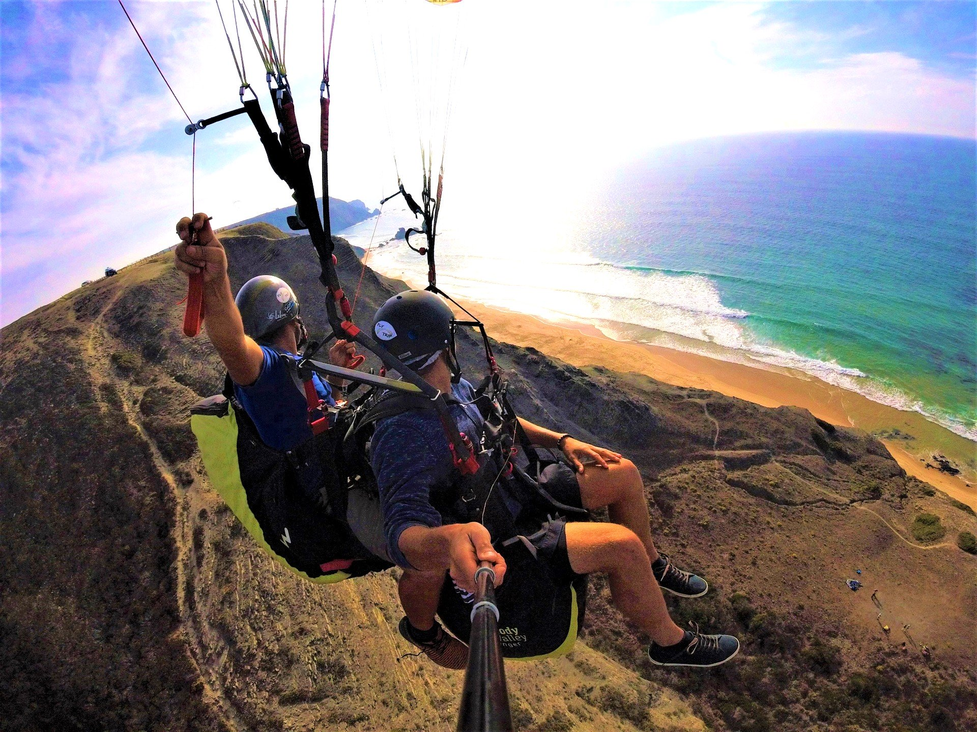 During a paragliding flight in the Algarve, the participant makes a selfie where you see him, the pilot and the coast of Portugal.