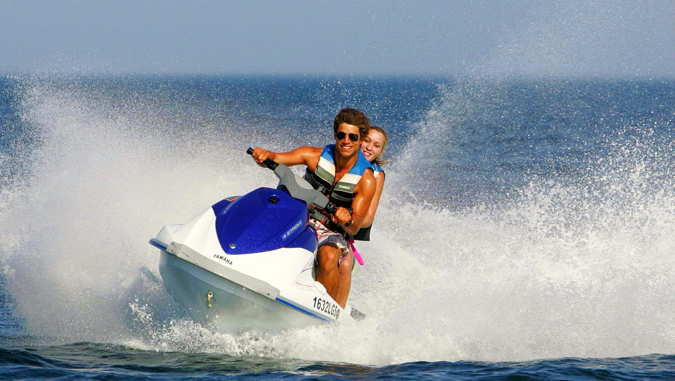 Two people enjoy driving a jet ski in the Algarve.