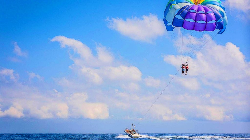 Two people do parasailing near Barcelona with a very colorful parachute, a beautiful outdoor activity near Barcelona.
