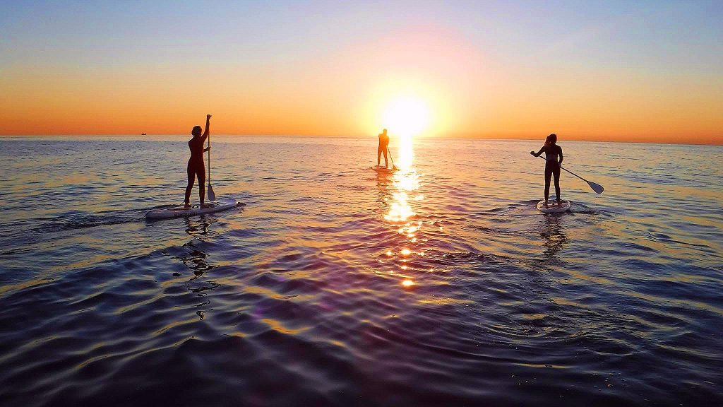 Three persons do SUP in Barcelona during sunset, a beautiful outdoor activity in Barcelona.