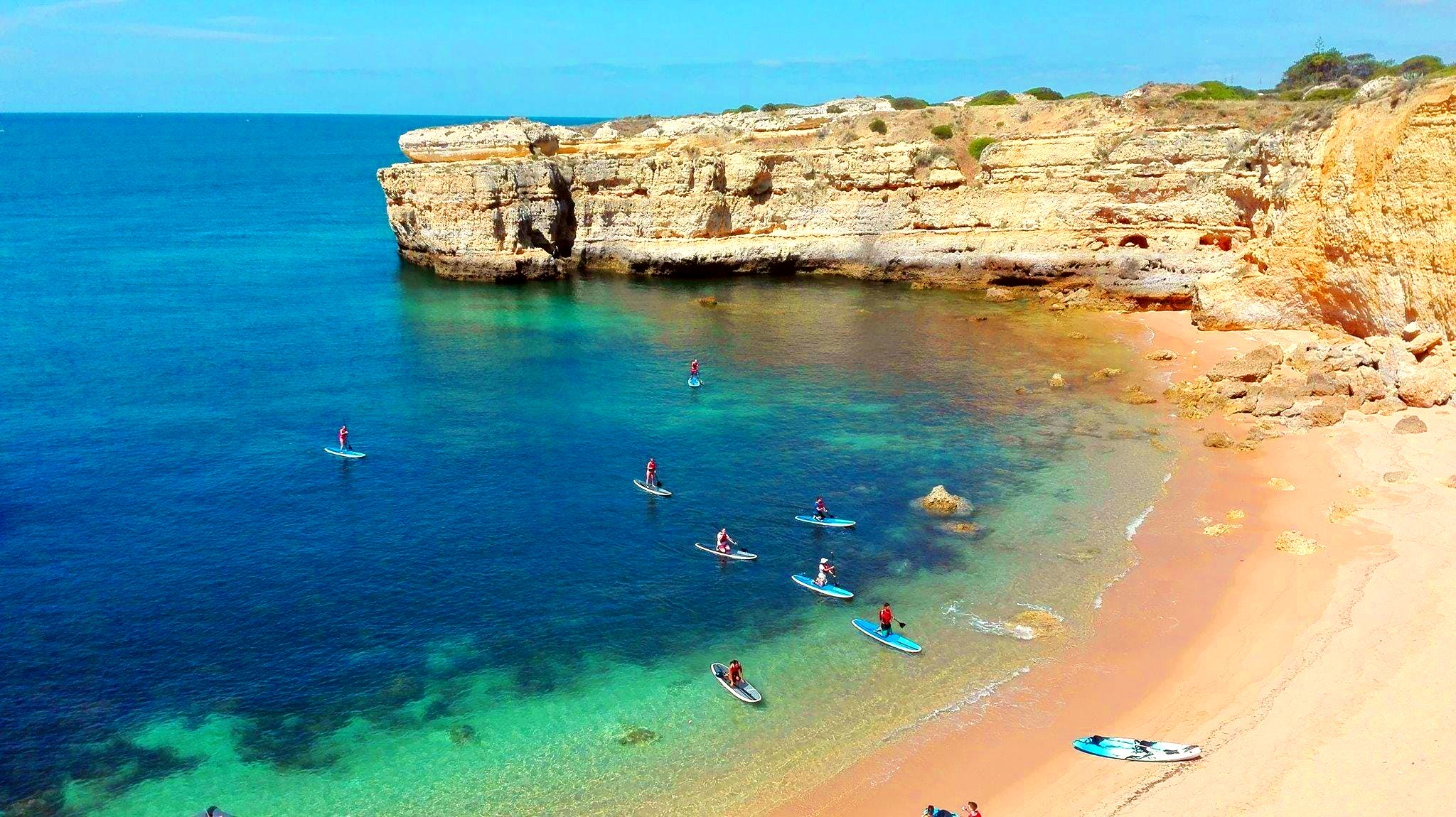 A group of people are coming to a beach during a sup tour in the Algarve.