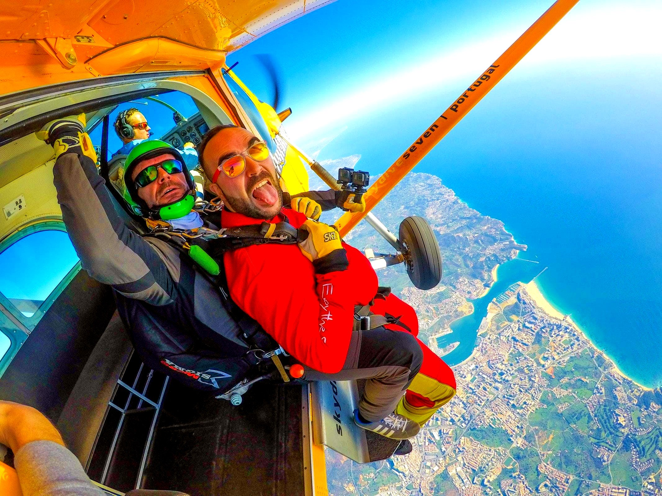 The plane has the door open, the participant and his instructor are ready to skydive in the Algarve.