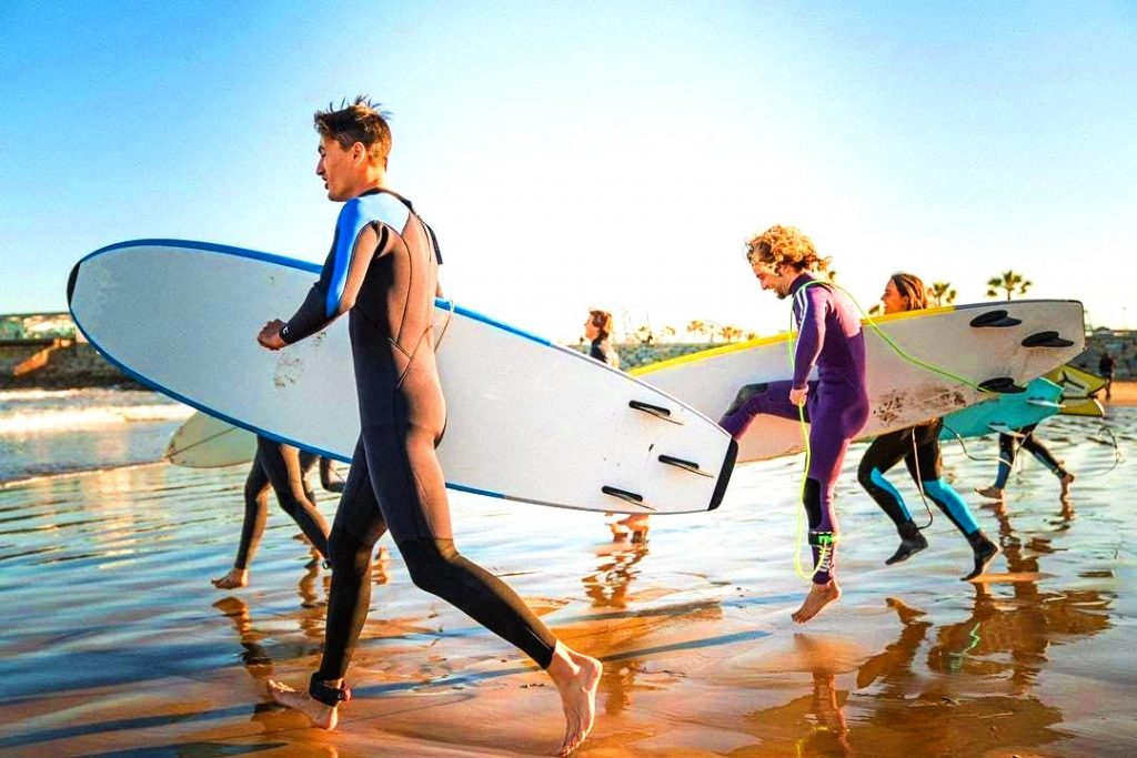 Five guys run with their surfboards under their arms while participating in a surfing lesson in Barcelona, a beautiful outdoor activity in Barcelona.