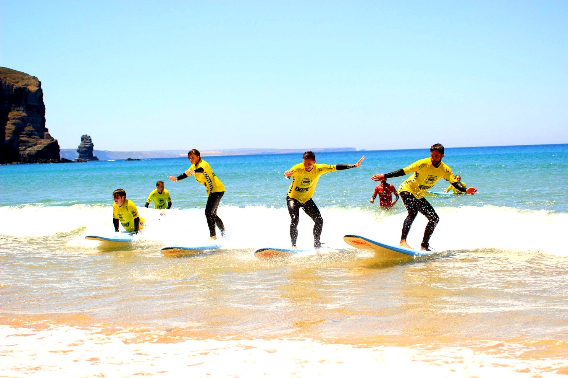 Five guys are surfing in the Algarve.