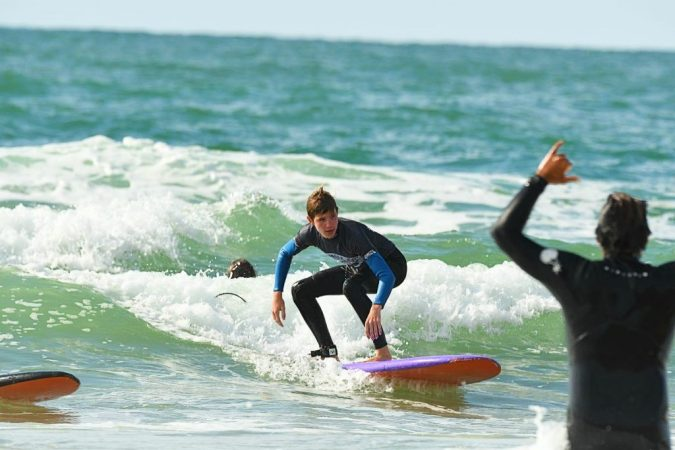 A guy faces the waves during a surfing lesson in Biarritz.