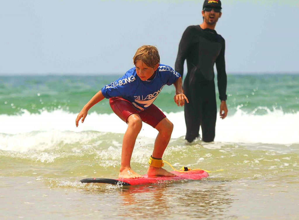 A child stays balanced on the surfboard while the surf instructor gives him advice during the surfing lesson in Hossegor.
