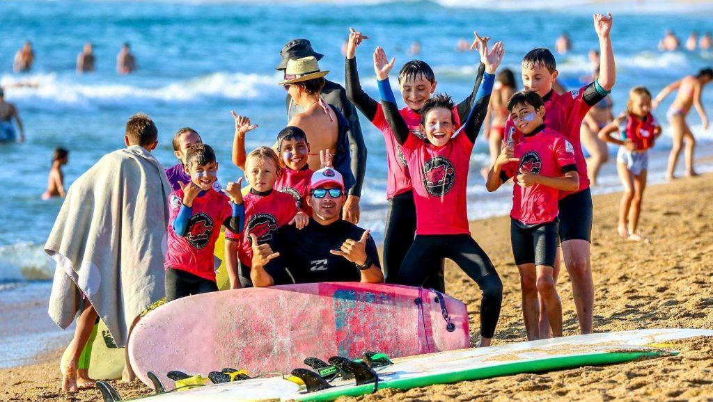 Un groupe d'enfants sourit avec leur moniteur à la fin d'un cours de surf à Hossegor.