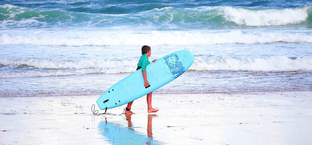 Un jeune homme marche le long du rivage après son cours de surf à Seignosse.