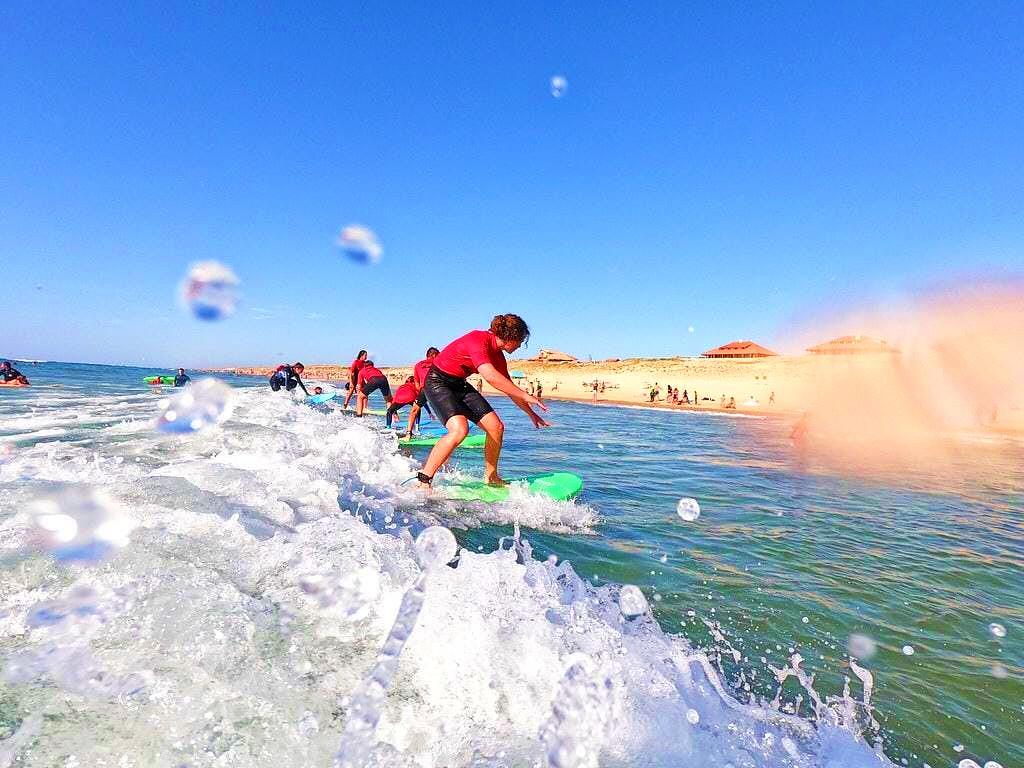 Des adolescents surfent leur première vague pendant leur cours de surf à Vieux Boucau.
