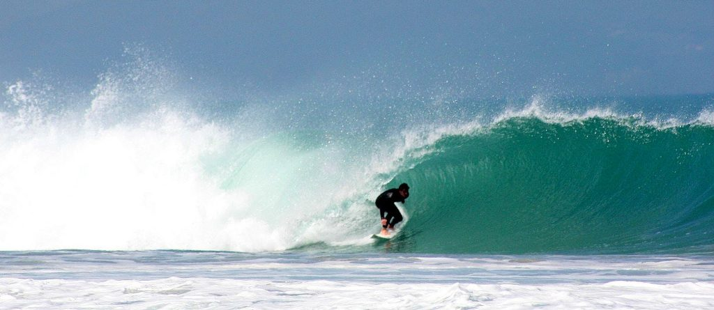 A boy faces the waves while surfing in Anglet.