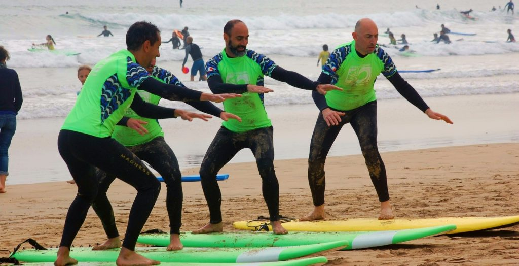 The surf teacher shows how to be on the board to 3 beginners who are taking a surfing lesson.