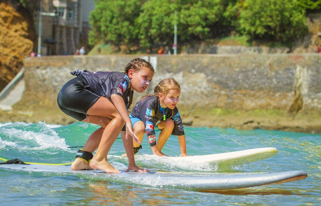 Two girls are trying to keep their balance during a surfing lesson in Biarritz.